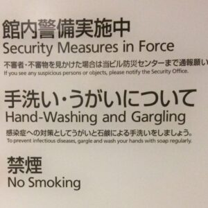 A public sign in Japanese imploring people to wash their hands and that security is in place