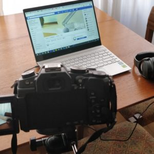 Camera recording a laptop with headphones next to it
