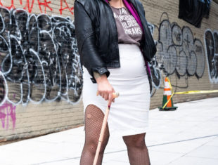 A brown person with long black, grey and blue hair smiles askance from the camera. They wear glasses, tall boots, fishnet stockings, a white skirt and a balck leather jacket. They're standing with a cane on a white tiled pavement with a graffitied brick wall behind them.