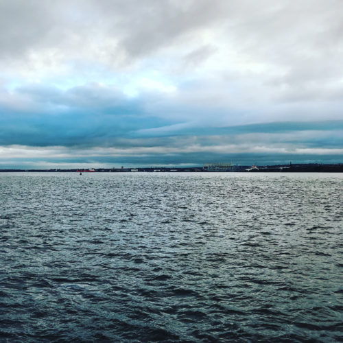 A large body of water and an overcast sky
