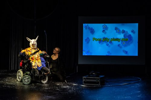 The artist is in a wheelchair and wearing a rabbit mask and yellow shirt. To her side is her assistant. There is a screen to the right with the word 'Poor pity, pissy me' projected onto it.