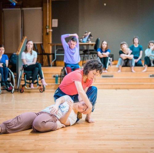 A woman wearing a pink tshirt and blue jeans crouches on the floor holding the head of another woman who is laying on the floor with one leg bent up underneath her. She wears a white tshirt and lilac trousers.