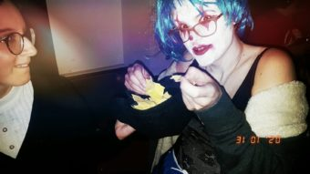 The image shows Amy McCauley in a blue wig and white face paint. She has smudged red lipstick on and harlequin diamonds jutting through her eyes.
