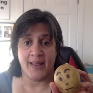 Woman holding a potato up to the camera