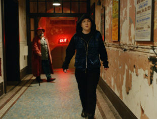 A person walks down a corridor in a building that has paint peeling off the walls. The person wears blackboots, dark trousers and a dark coat with the hood pulled up over their head. In the back ground there is a bearded man wearing a red hat, red coat, blue jeans and a green shirt. They are holding using a walking stick