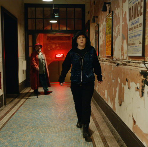 A person walks down a corridor in a building that has paint peeling off the walls. The person wears blackboots, dark trousers and a dark coat with the hood pulled up over their head. In the back ground there is a bearded man wearing a red hat, red coat, blue jeans and a green shirt. They are holding using a walking stick.