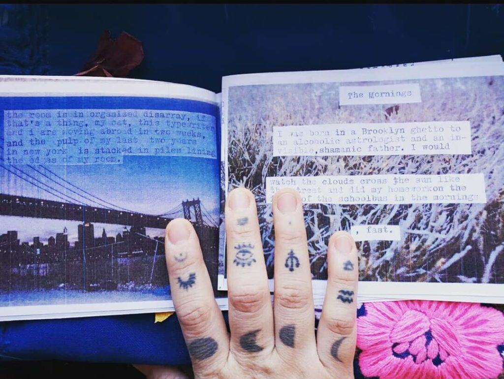 Tattooed hand holding open a zine which depicts New York city and a grassy field with text overlaid. On the left page is a night picture of the Brooklyn Bridge. On the dark blue sky, typewritten text appears printed on the page: 'the room is in organized disarray, if that's a thing. my cat, this typewriter and i are moving abroad in two weeks, and the pulp of my last two years in new york is stacked in piles lining the edges of my room.' On the right page is a picture of a snowy tree in winter, in close up, showing the branches looking white. Typewritten text appears printed on the page: 'The Mornings. I was born in a Brooklyn ghetto to an alcoholic astrologist and an invisible, shamanic father. I would watch the clouds cross the sun like the street and did my homework on the front of the schoolbus in the mornings, fast.' Bani's hand covers some of each page, and displays multiple symbol tattoos on their fingers, including the phases of the moon, the USB logo, and the zodiac sign of Aquarius.