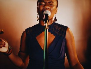 Tobi Nicole Adebajo is a black person with short hair wearing a purple dress and singing into a microphone expressively
