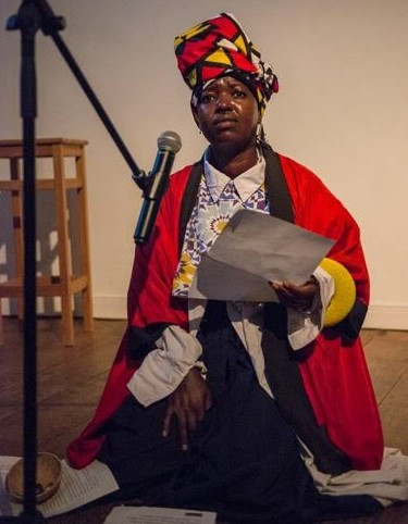 Skye Chirape is a black woman wearing a red, yellow, white and black headdress, red cape and patterned white shirt. She kneels on the floor at a microphone clutching a piece of paper.