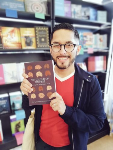 Andrés N. Ordorica is a Latinx writer with black glasses, short hair and beard. He wears a red tshirt and navy jacket, and holds a copy of a book as he smiles at the camera.