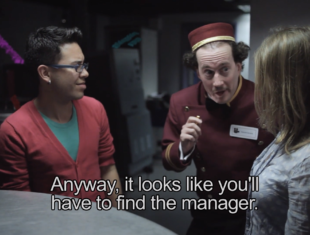 Film still showing a cinema usher leaning in to two customers. The subtitles read Anyway, it looks like you'll have to find the manager