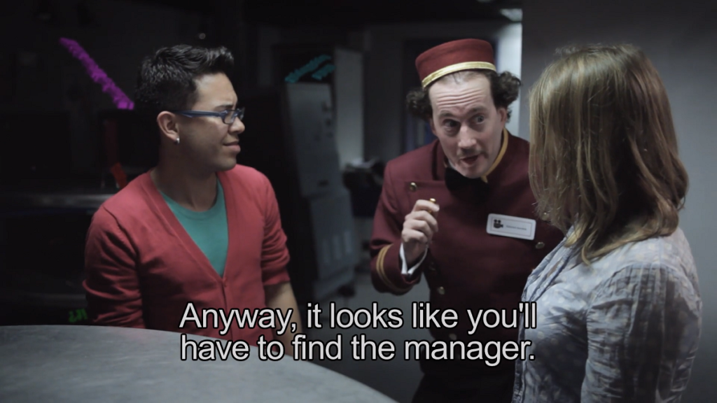 A still from Teresa Garratty's film, Admit None. A white cinema usher wearing a burgundy bellhop-like uniform and hat, with black curly hair on the sides of his head, leans in to two customers. A white woman is to the right of the frame, facing the usher and away from the camera, wearing a white blouse. To the left of the usher is a mixed-race Asian man with short black hair and a slight quiff. The man wears grey-blue glasses, a salmon pink cardigan and teal top. He is wincing at the usher. The subtitle of the usher reads: 'Anyway, it looks like you'll have to find the manager.'
