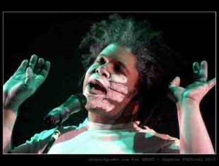 Black performer with hands held aloft, a white chalk hand is imprinted across their face as they speak into a microphone