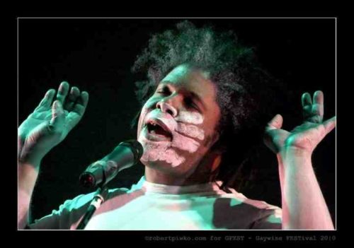 A Black performer with a small afro and wearing a white tshirt. His hands are held up as if holding something or pushing upwards. A white chalk hand is imprinted across his face. He speaks into a microphone with eyes closed.