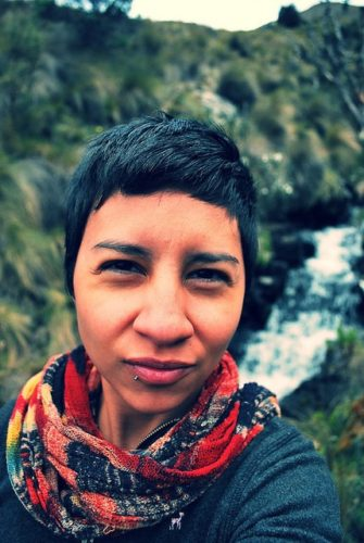 Bani Amor is an Ecuadorian/Guatemalan-American. They have short dark hair and a lip piercing. They stand in front of a waterfall wearing a bright, multi-coloured scarf.