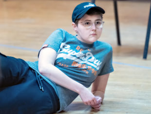 an actor wearing a blue t-shirt and baseball cap lies on the floor of a stage, looking away from the camera with an expression of concentration