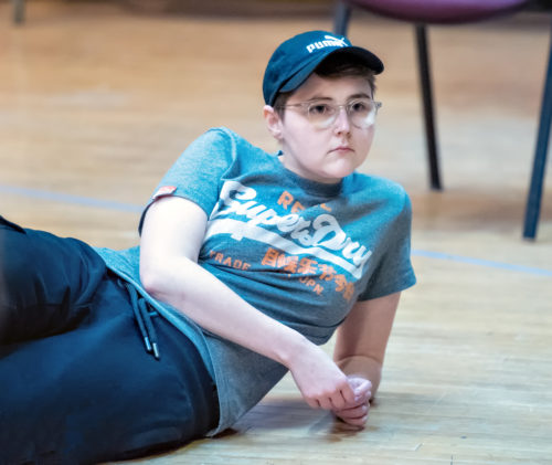 Brooklyn Melvin, a white actor with short hair and glasses. They wear a blue t-shirt and baseball cap. Brooklyn lies on the floor of a stage, propped up on one elbow and looking away from the camera with an expression of concentration.