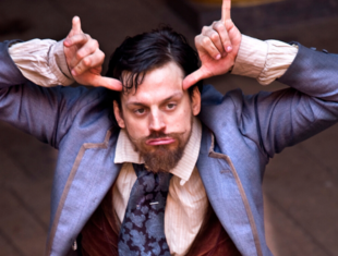 A man wearing a blue jacket, light shirt, blue neck tie and red waistcoat. He has dark hair and a beard. His hands are raised to his head, his fingers folded whilst his thumb and little finger are outstretched - BSL for Cow.