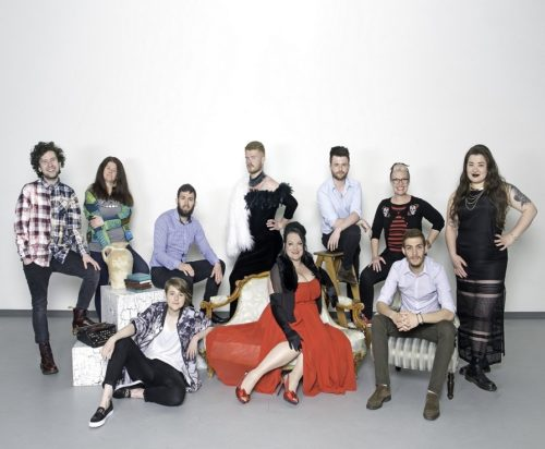 A group of ten people pose, smiling or looking at the camera, seated or standing within a studio. The floor is grey and the back wall a neutral off-white. Front centre a white woman wears a bright red dress. Brooklyn is to her left sitting on the floor, they're a white person wearing black trousers and a button-down shirt. Bea Webster is on the far right, wearing a long elegant black dress. She is Scottish-Thai with long brown hair.
