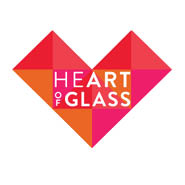 A geometric heart made up of pink, red and orange triangles. In the middles reads Heart of Glass in white.