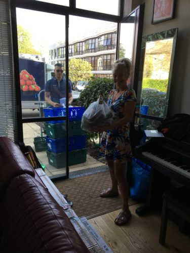 Liz Bentley missing the pAWhite woman holding a bag of shopping whilst a Tesco Delivery man waits with crates of shopping at the door