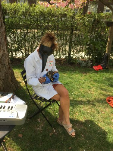White woman in crows mask, white shirt playing a ukelele in a garden