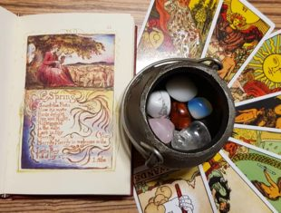 Illustrated poetry book next to a fanned circle of tarot cards with a small cauldron of semi-precious stones