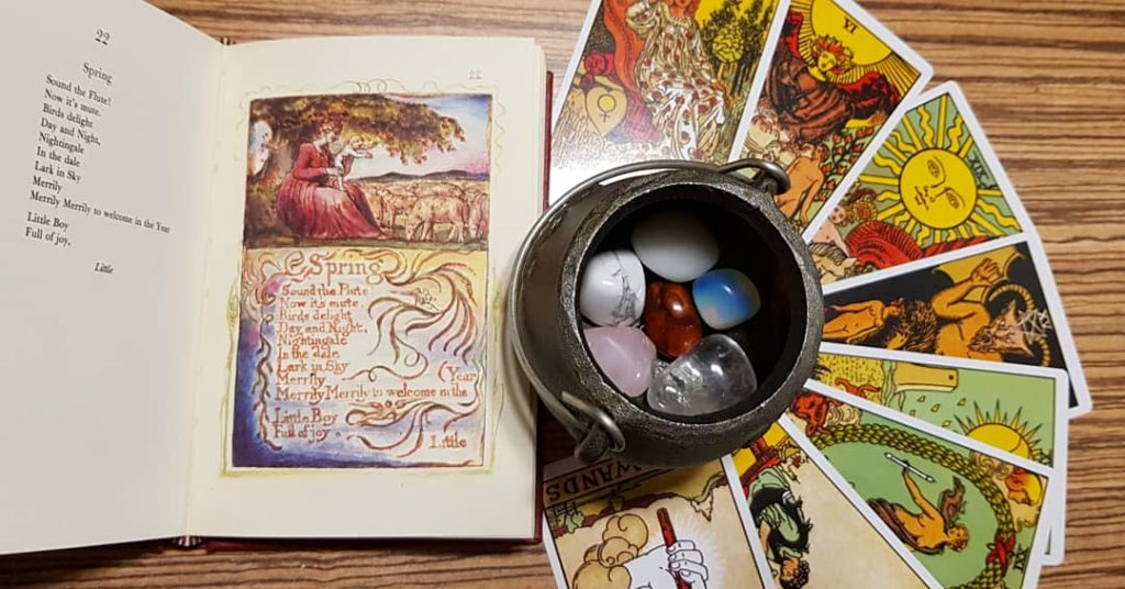 Illustrated poetry book next to a fanned circle of tarot cards with a small cauldron of semi-precious stones. On the left of the photo is an open book of poetry, showing William Blake's poem, 'Spring' on the left page. The right page show the same poem within an illustration. Above the poem is an image of a woman in a red dress sitting under a tree with a baby in hand. The baby is standing up on the woman's knees, and has their arms outstretched towards a flock of sheep seen in the background. In the centre of the altar is a small metal cauldron containing several precious stones of different colours. Arranged in a fan-like fashion underneath the book are eight Tarot cards. In clockwise order: The Empress, The Lovers, The Sun, The Devil, The Moon, The Wheel of Fortune, Eight of Pentacles and the Ace of Wands.