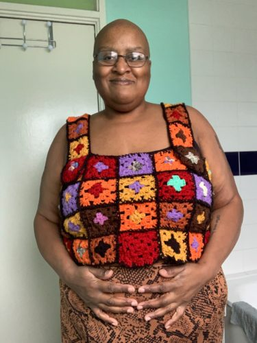Jacq A is a non-binary Black person with a shaved head, glasses and a colourful knitted top. Jacq is a fat activist, and in this photo they are smiling at the camera and with their hands on their stomach.