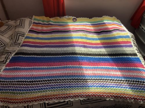 A crocheted flag blanket in rainbow colours. The blanket contains the rainbow flag with the additions of the colours of black and brown, as well as the trans colours of pink, blue and white, and bi colours of pink, purple and blue. There are other colours to represent groups often left out of 'gay' pride.