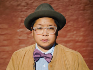 A 'brown round queer' with short hair and glasses stares intently at the camera. They wear a dark trilby hat on their head and sport a brown jacket and purple bow tie.