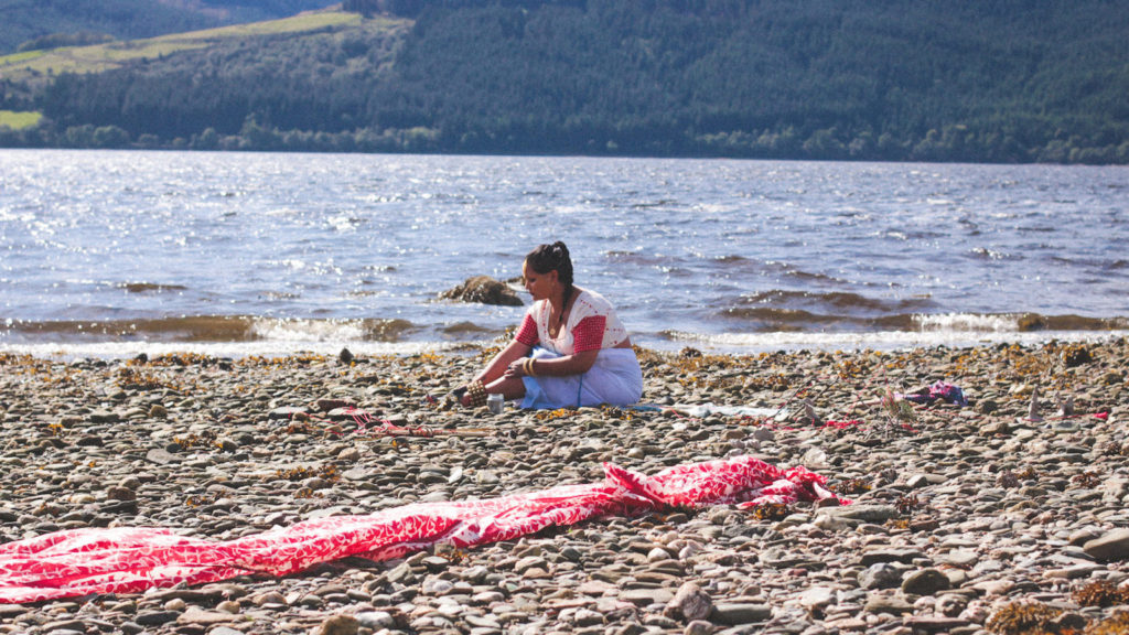 South Asian queer disabled femme sits on a pebbled beach with water behind her. In the foreground of the image a red and white piece of textile is strewn on the pebbles.