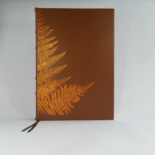 Brown self-bound book. The cover is an earthy brown fabric with fern leaves in orange thread.