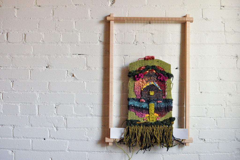 Green textile artwork hangs from a loom attached to a white-brick gallery wall. The weaving takes the shape of a black person's face.