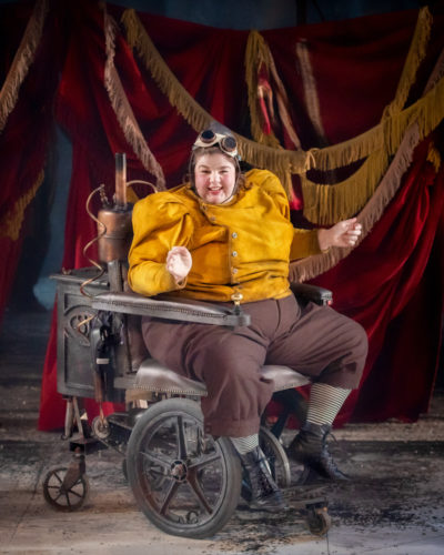 Steph Lacey, a white actor dressed in an ochre and brown steam-punk outfit, smiles at the camera. Steph is sat in a steam-powered wheelchair.