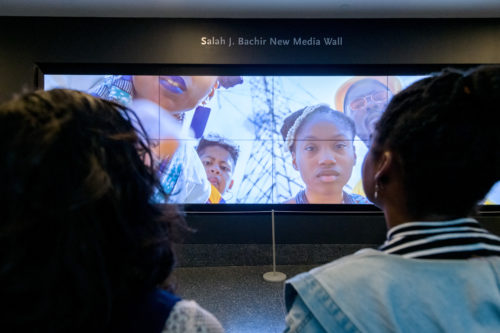 The photo is taken from behind the front row of the audience. Two people of colour watch a large banner-shaped screen on the Salah J Bachir New Media Wall. From the screen, four Black faces lean down towards the camera, as if it's on the ground. They're dressed in bright colours, and have futuristic styled clothing. The most clear face is of a young person with a serious expression. Behind them, electricity towers and a blue sky.
