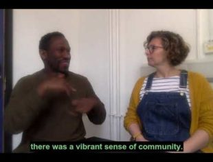[Video image description: David Ellington is on the left and Lynn Stewart-Taylor on the right. David is a Black man with short, brown curly hair. He's wearing a dark green sweater. Lynn is a white woman with brown bobbed and curly hair. She's wearing red glasses, a yellow cardigan, overalls and black and white striped top. Green captions say: There was a vibrant sense of community.]