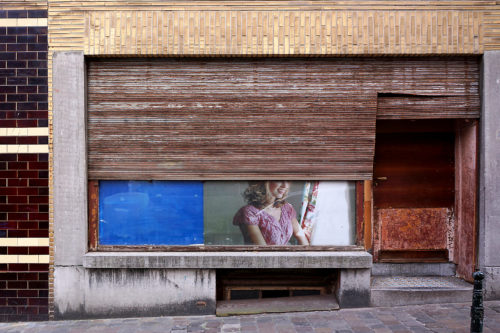 Photograph showing a front view of a half boarded up shop with the shutter half open and a fastion poster of a woman dressed in pink peeping out from under the shutter
