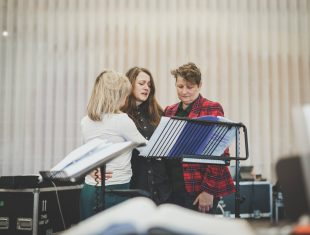 Three white women in rehearsals looking at a sheet of music on a stand. One is blonde with face onscured, the other has long brown hair, the third has short brown hair and a tartan suit jacket
