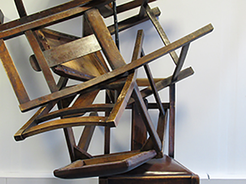 Image of randomly stacked wooden chairs. Stacked in a chaotic manner