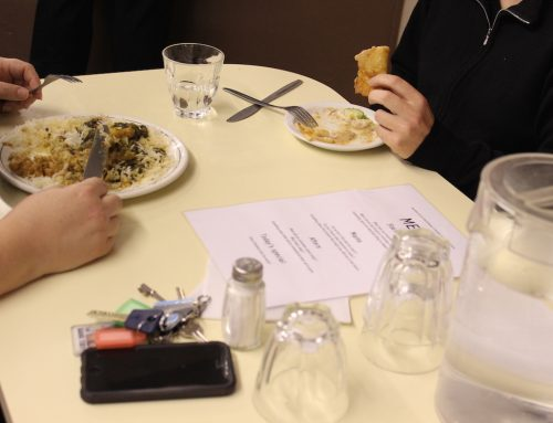 A table at a restaurant. There are two people eating, you can only see there hands and their plates of food. Next to them on the pale yellow table is a paper menu, a salt cellar, bunch of keys, a mobile phone, 2 upturned glasses and a jug of water.