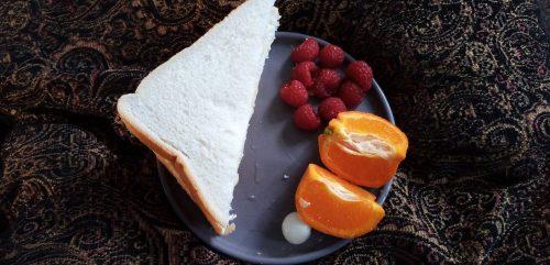 photo of a sandwich, orange segments and raspberries on a plate