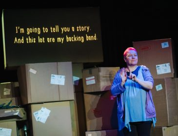 "A person stands in front of a large stack of cardboard boxes. There is a screen above the boxes and on it is written ""i'm going to tell you a story. Ans this lot are my backing band."""