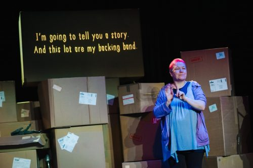 """A person stands in front of a large stack of cardboard boxes. There is a screen above the boxes and on it is written """"i'm going to tell you a story. Ans this lot are my backing band."""""""
