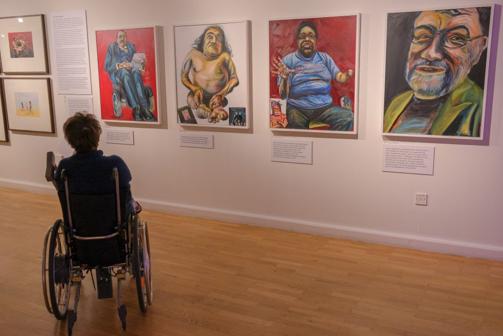 WHeelchair user looking at a series of oil portraits of prominent figures within the disability arts movement