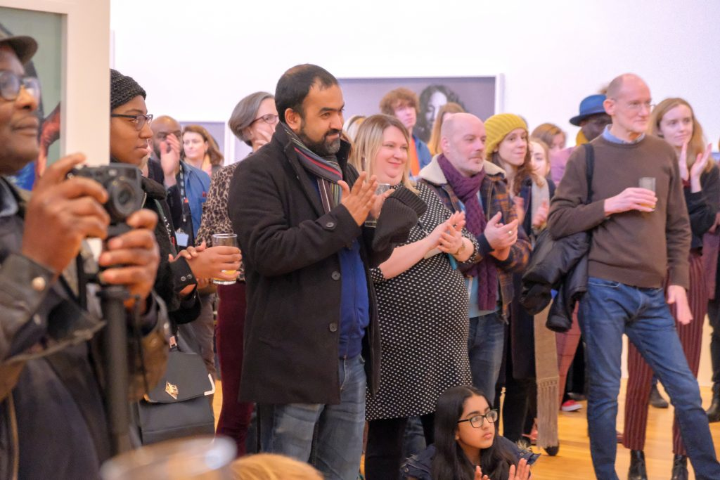 Group of people clapping whilst stood at an exhibition opening