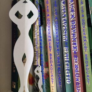 Paper ballerina propped up against books. All of their titles have been changed to read This is a Government Broadcast