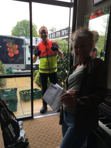 White, ginger Tesco Delivery Man standing in a front doorway giving thumbs up as a white blonde woman smiles next to a piano.