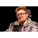 A white individual with short ginger hair and beard. They have red thick rimmed glasses and are wearing green glittery eye shadow and pink lipstick. They are wearing a silver coat and a black t shirt.