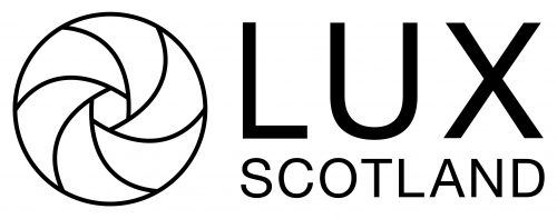 A white background with a black outline of a circle. Within the circle there are black curved lines heading towards a small hexagon in the centre. Next to this is LUX in large black capitals. Below in slightly smaller type is Scotland in black capitals.